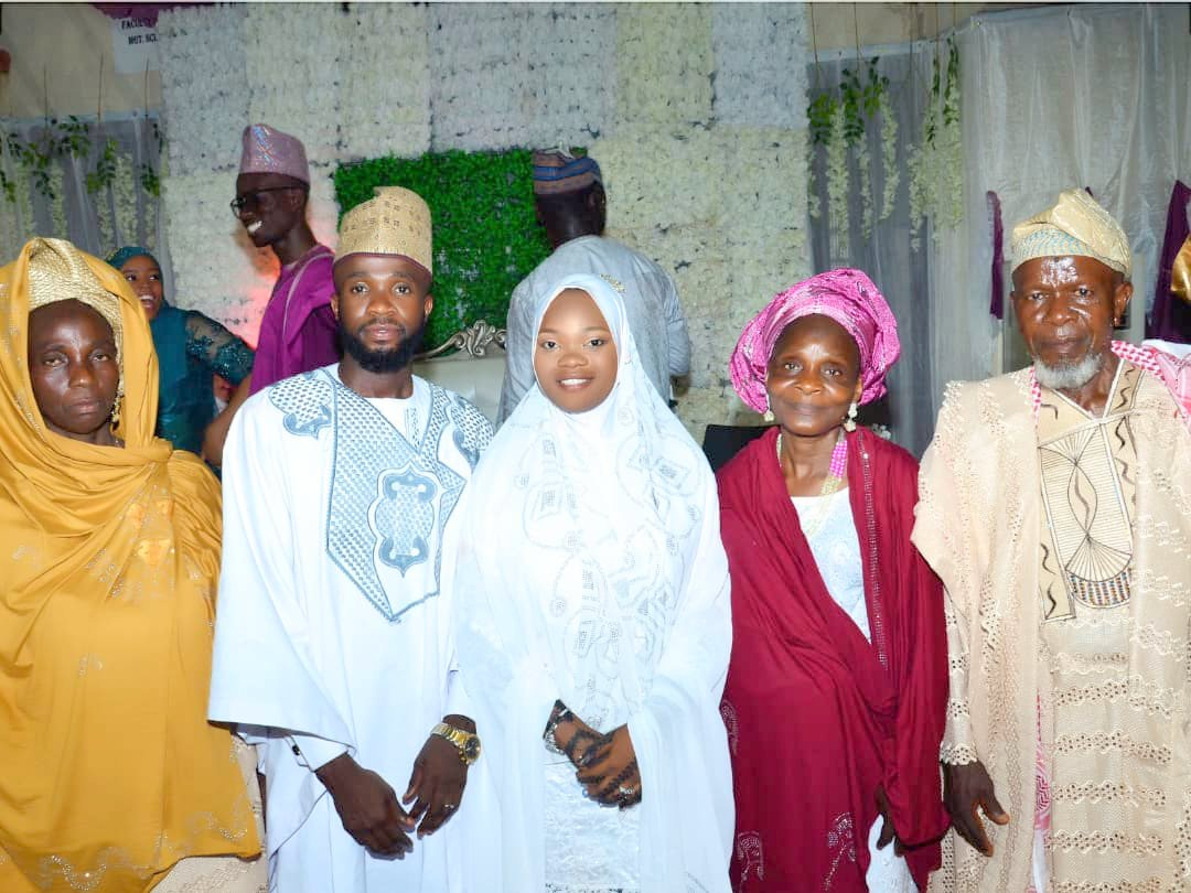 The couple flanked by the groom's parents alongside a family member