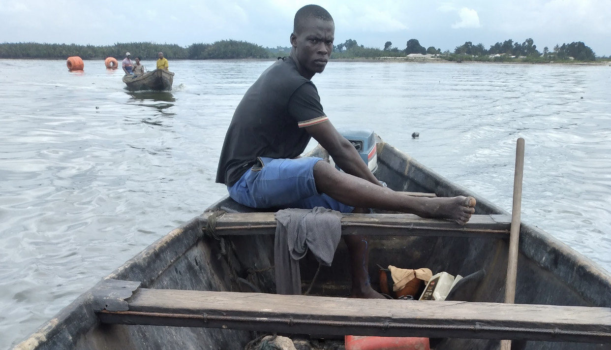 Joel Obinna has to carefully meander his way to avoid destroying his boat's propeller. Photo Credit: Beloved John