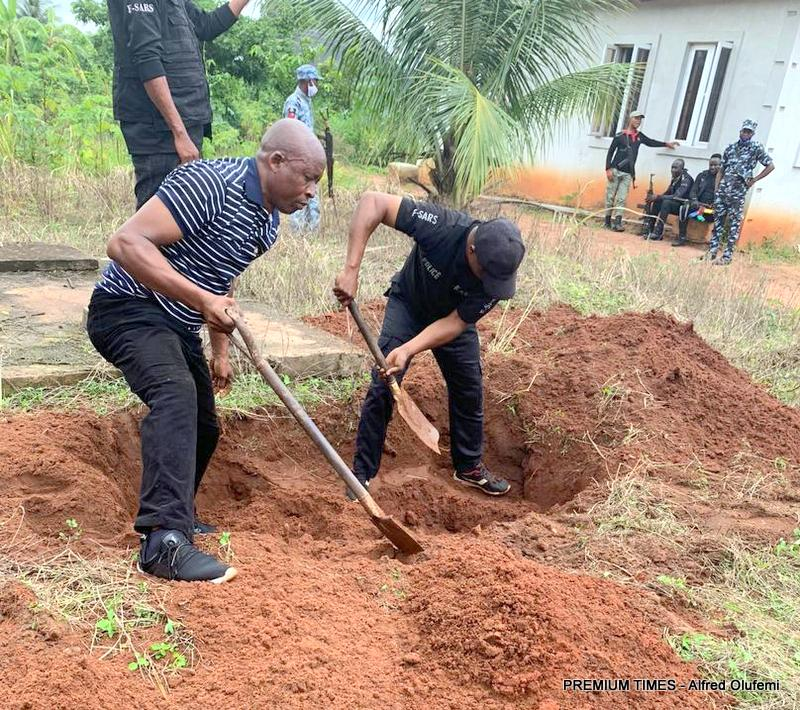 Police operatives supervising the exhumation process