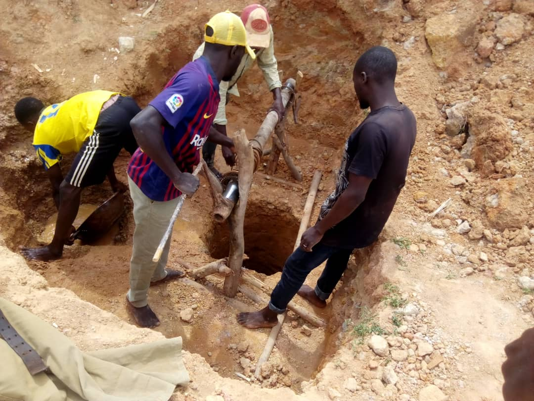 Miners extracting tin from a hole