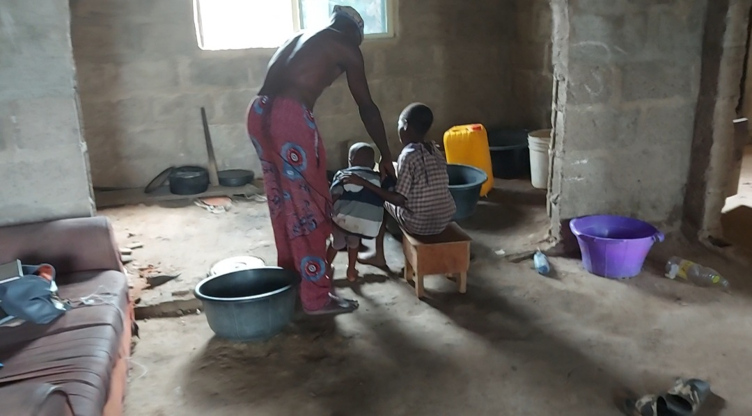 A back view of Samuel Akinbodewa, the 77-year-old father of the detained woman and his two grandchildren.