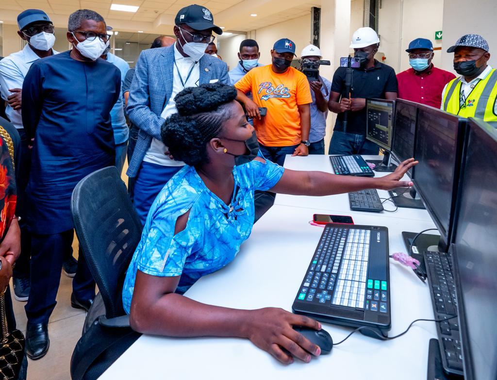 L-R: President, Dangote Group, Alhaji Aliko Dangote and Lagos State Governor, Mr. Babajide Sanwo-Olu, being shown an electronic programming by a Process Engineer, Dangote Fertilizer, Kemi Laoye during the Governor's working visit to Dangote Fertilizer at the Lekki Free Trade Zone, Ibeju-Lekki, on Saturday, March 20, 2021.