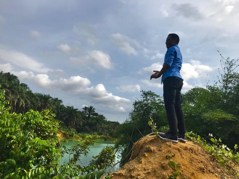 Anietie Usen climbs a hill to have a better view of the green river
