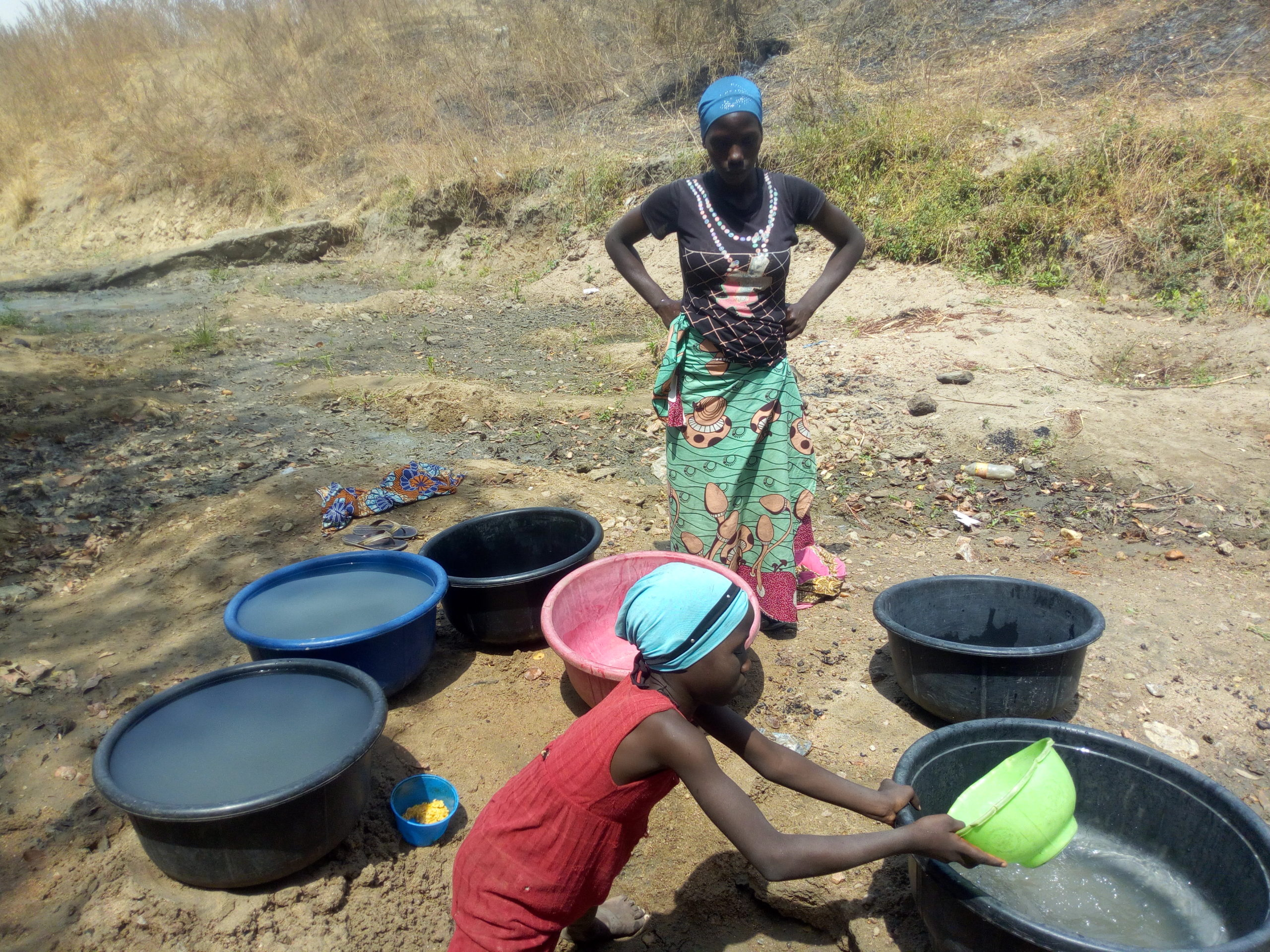 A housewife and her 8-year-old daughter scooping muddied water for domestic use at Wuna community.