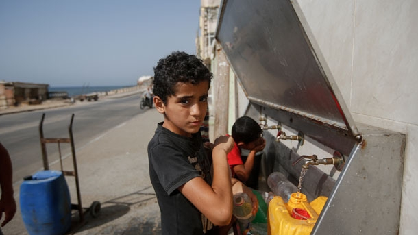 A boy with dark hair fill a jug of water at a tap provided by a mosque