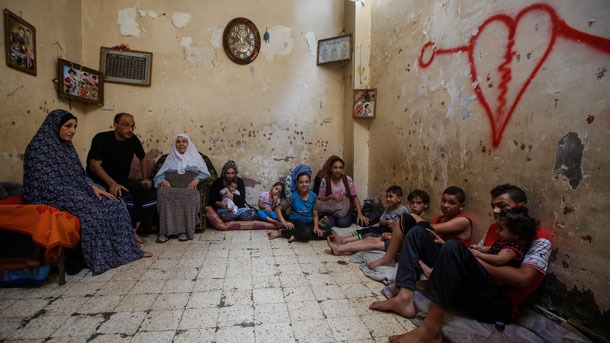 Fifteen family members in Gaza sit in the living room with a red heart spray painted on the cream-colored wall.