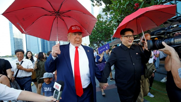 Men impersonating North Korean leader Kim Jong-un and US President Donald Trump meet at Merlion Park in Singapore, June 8, 2018.