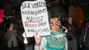 "A woman holds a sign that says ""Sex workers and residents against police raids and closures."""