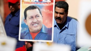 Venezuela's President Nicolas Maduro greets supporters next to a placard with an image of Venezuela's late President Hugo Chavez, at Miraflores Palace in Caracas, Venezuela May 24, 2016.