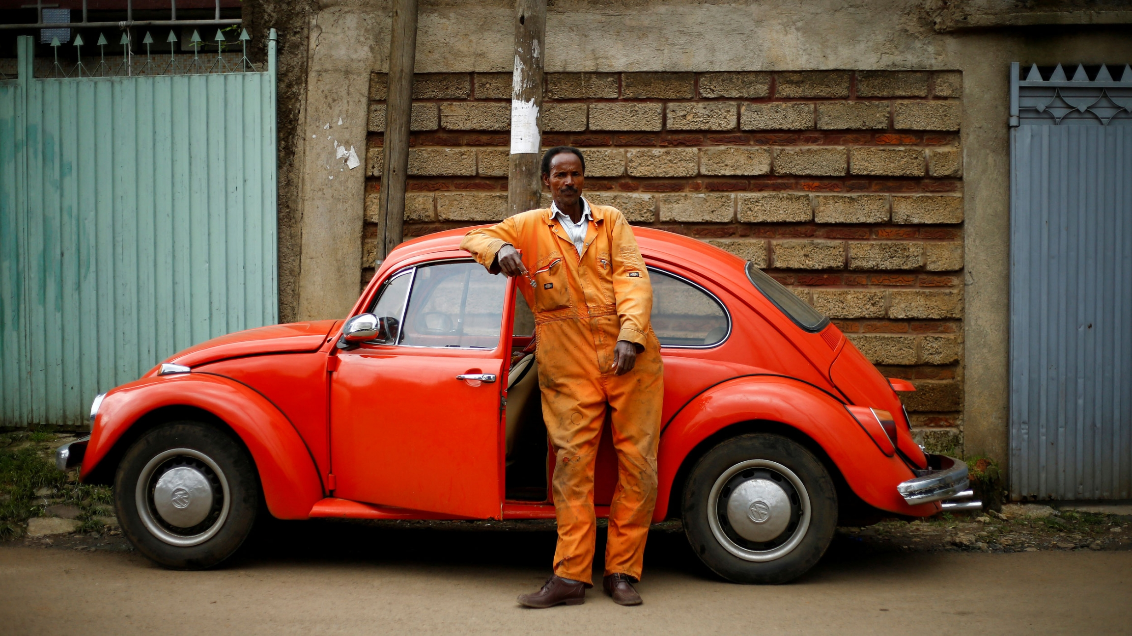 a man in an orange jump suit leans his arm on a red 1965 model volkswagen [ 2304 x 1296 Pixel ]