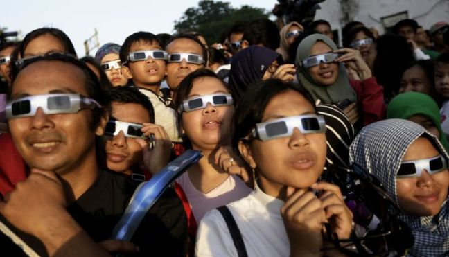 people wearing protective glasses look up at the sun to watch a solar eclipse