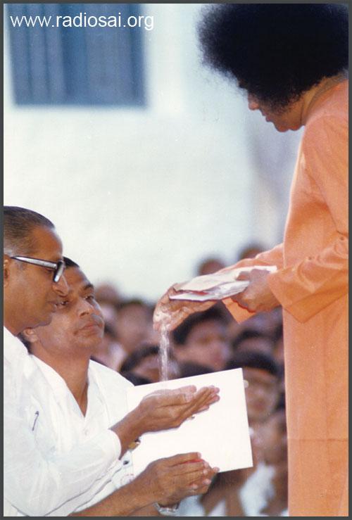 sathya sai baba giving vibhuti to devotess