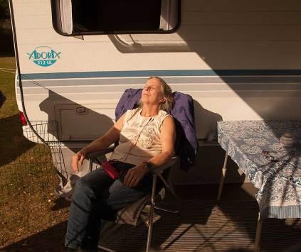 Irene med ljudboken och en skön stol i solen.