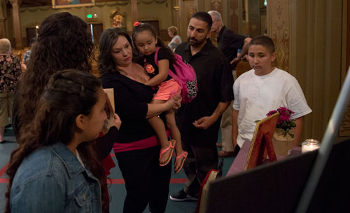 Teresa Valdivia, with her husband and family, takes in photos of her grandmother, Genevieve Lucchesi, at her memorial service. The picture board reflected Genevieve's two lives, from vibrant young mother to a worn and disheveled homeless woman.