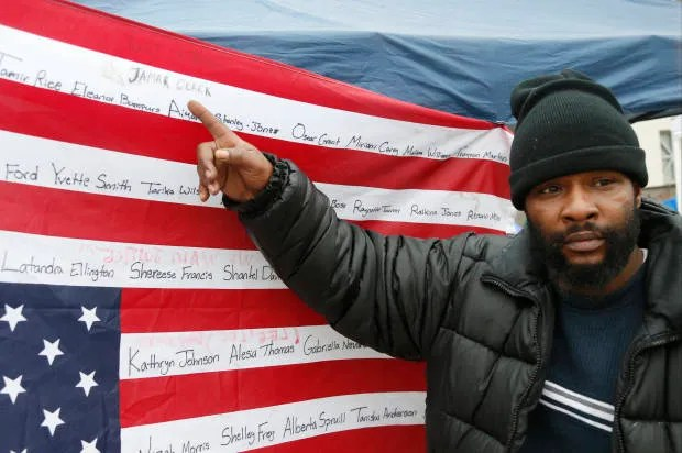 Jamine Robinson points to the name of his brother, Jamar Clark, on an upside-down flag bearing names of people killed at the hands of police. A shooting erupted last night at that Black Lives Matter encampment.(Photo credit: AP)