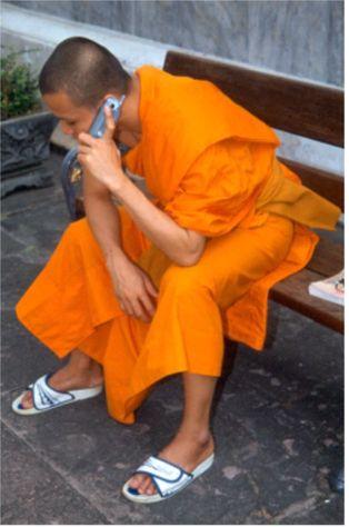 Munk med mobiltelefon. Bangkok