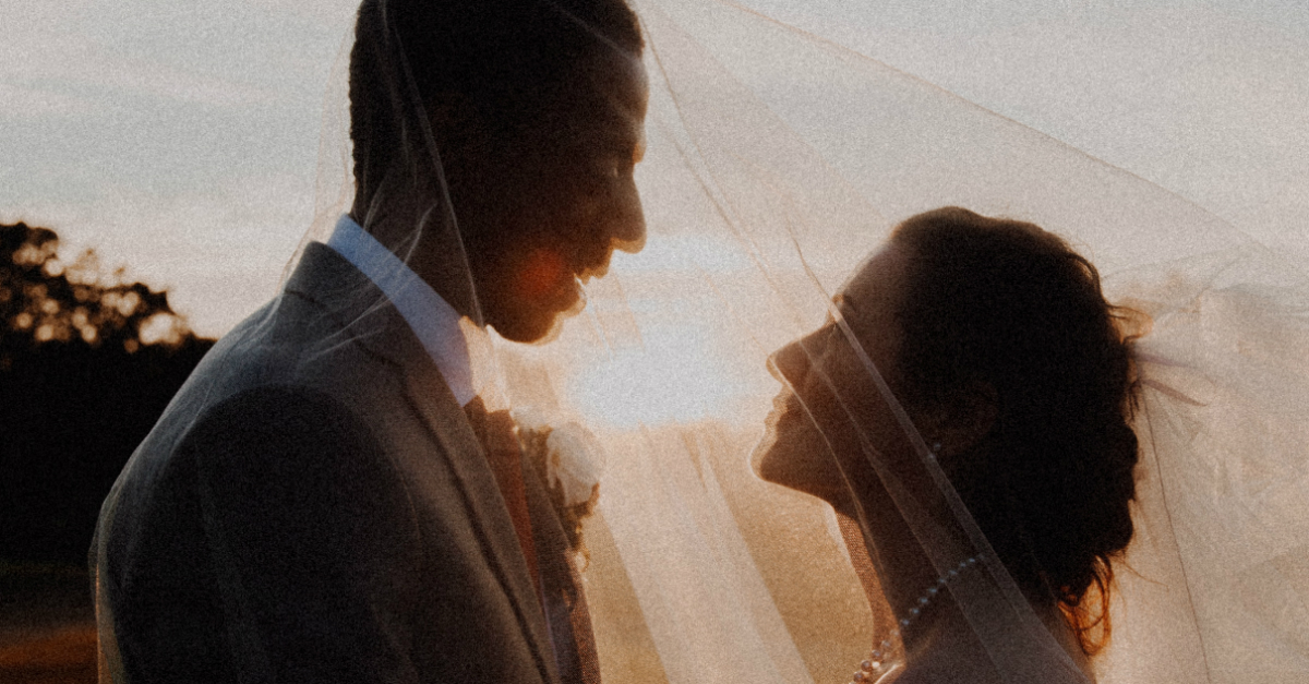 wedding couple looking at each other under a veil happy, ready to marry