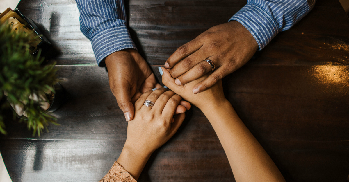 couple holding hands across table, shame undermines marriage
