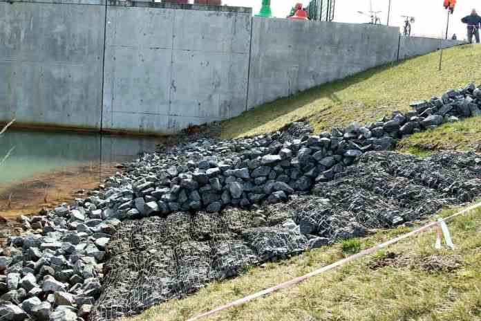 They had tried in vain to stabilize the sagging embankment with stone mats.  The sluice structure behind it could be undermined, so the fear of the experts.