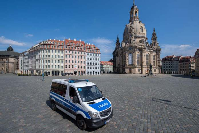 A police car drives across the almost deserted Neumarkt in front of the Frauenkirche.