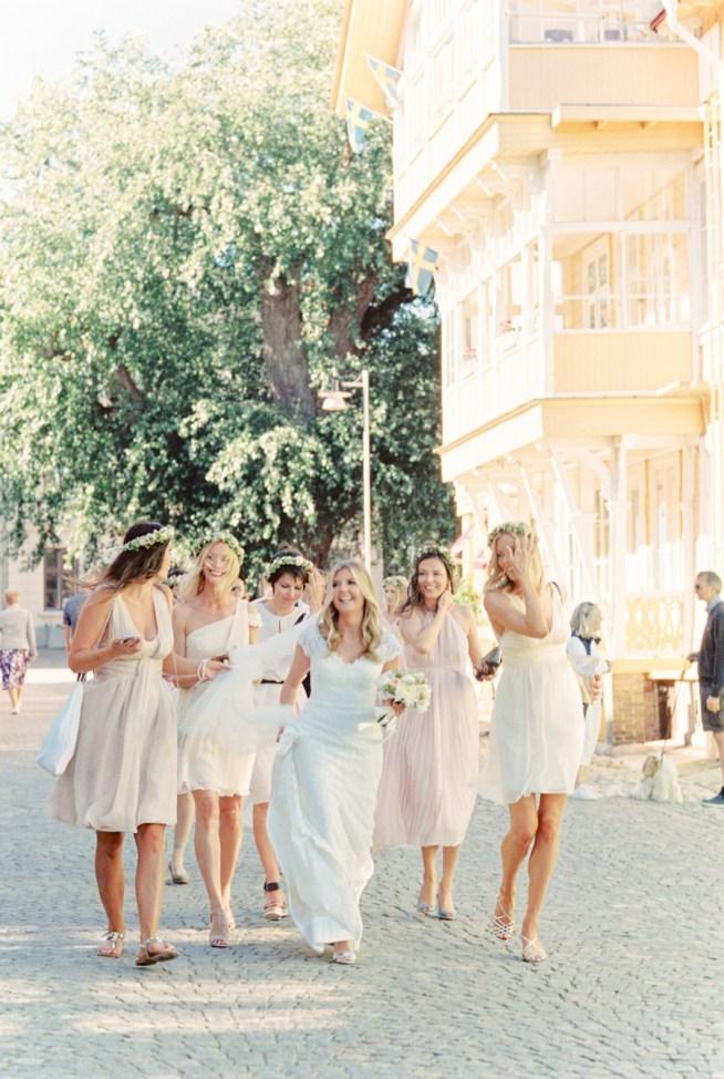 skrattande brudfölje med tärnor i rosa klänningar och hårkransar från the wild rose