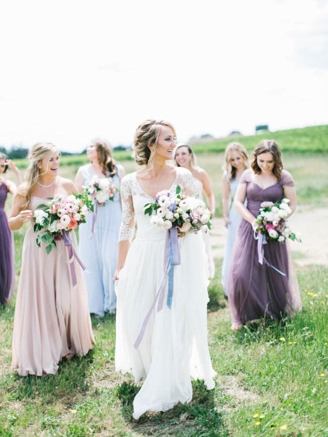 brud med brudbukett och tärnor i pastellklänningar