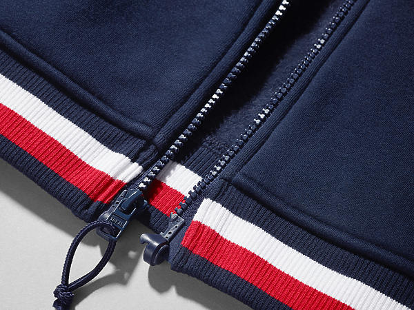 Image shows sweatshirt magnetized at the base, so wearers with limited dexterity can now zip and unzip with ease.