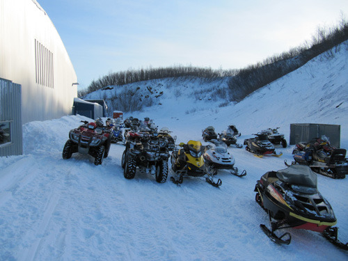 4 wheelers and snow machines parked outside a rural Alaska school in winter