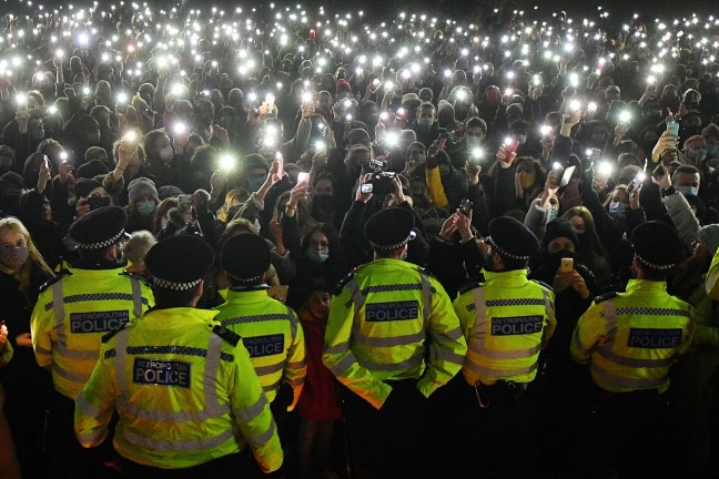 Police officers form a cordon as vigilgoers turn on their phone lights at a bandstand on Clapham Common.