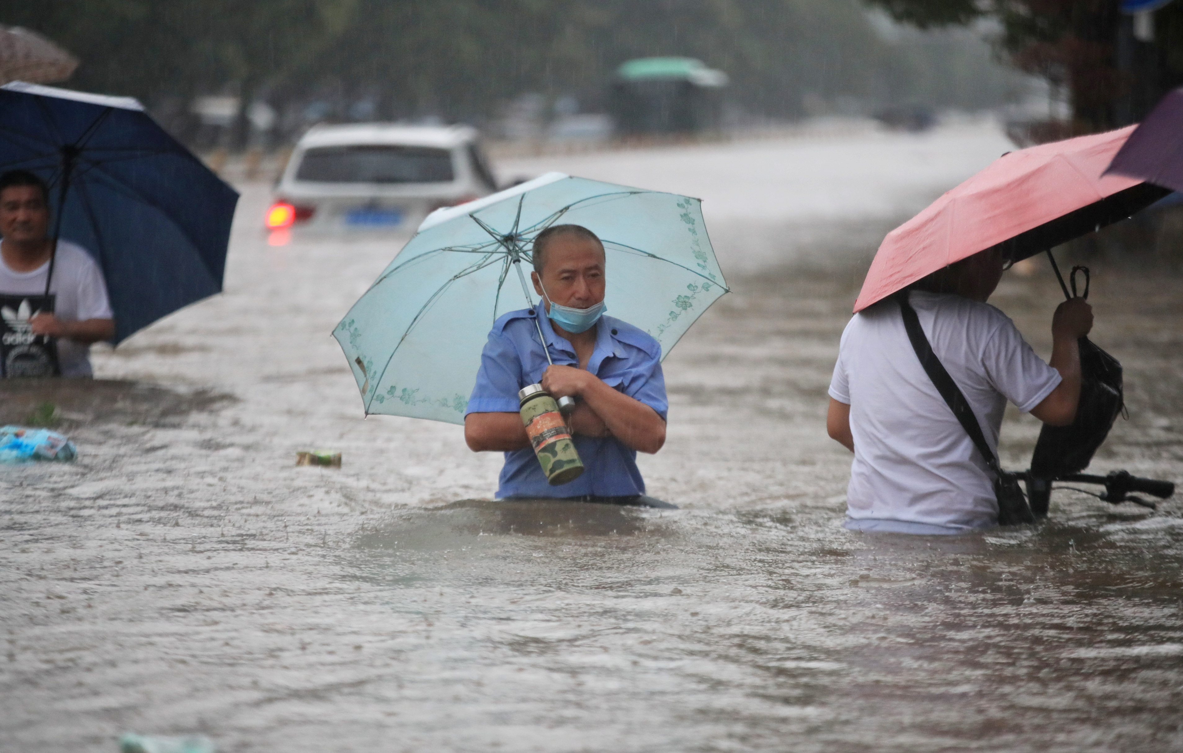 Residents wade through floodwaters on a flooded road amid heavy rainfall in Zhengzhou, Henan province, China July 20, 2021…