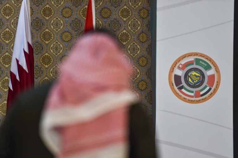 A Saudi journalist is pictured in front of the logo of the Gulf Cooperation Council (GCC) and the Qatari national flag at the…