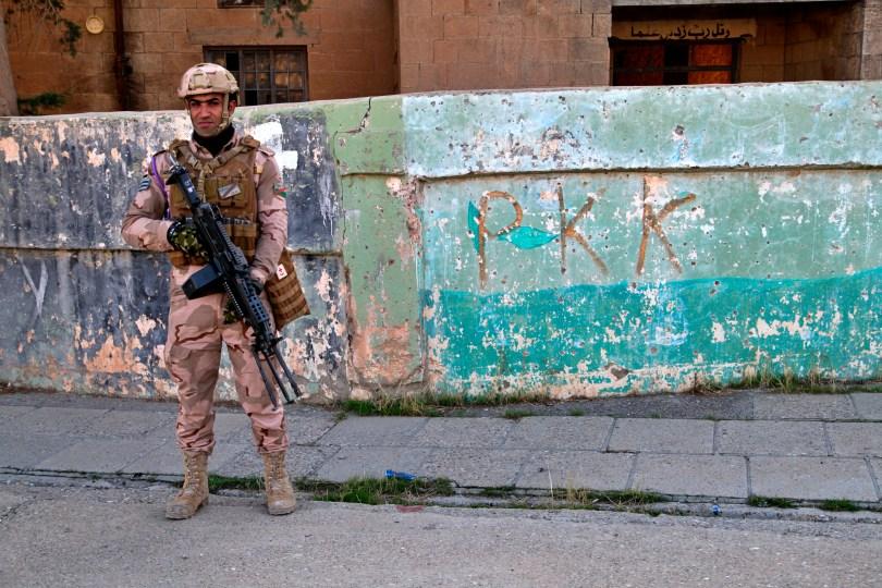 Un soldat irakien se tient à côté des graffitis laissés par une branche du Parti des travailleurs du Kurdistan, ou PKK, qui a récemment ...