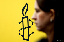 The logo of Amnesty International is seen next to director of Mujeres En Linea Luisa Kislinger, during a news conference to…