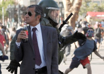 Backstory - As a Riot Rages, a Neatly-dressed Chilean Sips His Soda