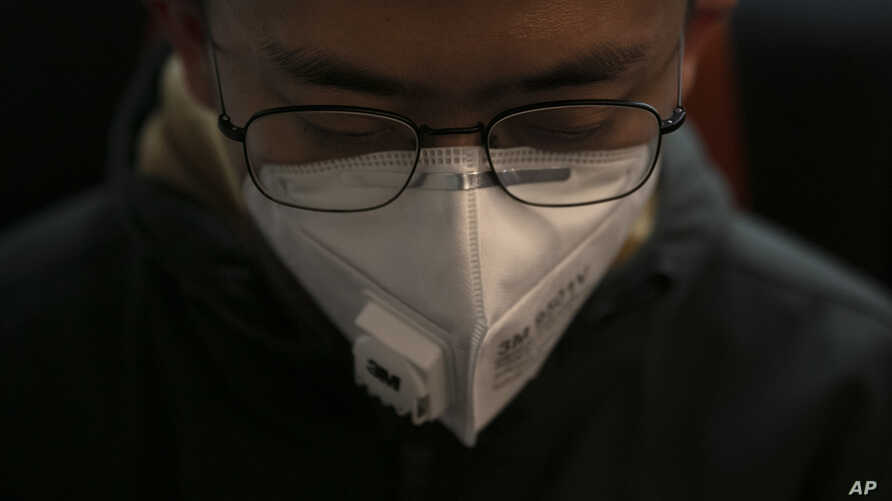 A man wears a mask as he travels on a train Wednesday, Jan. 29, 2020, in the Odaiba district of Tokyo. Japanese officials say…