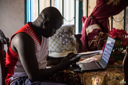 Junior Dau, 31, looks at photos of his cousin, who was killed in South Sudan's civil war, in Juba, South Sudan. (Chika Oduah/VOA)
