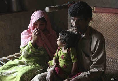 Pakistan's Tariq Ali, 30 along with his wife Parveen and three-year-old Ume Kulssom all infected with HIV sit at their home in a village near Ratodero, May,16, 2019.