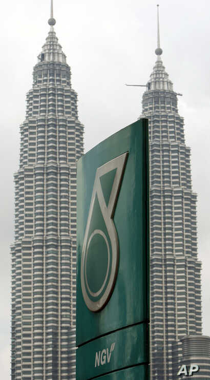 In this photo taken on Oct. 4, 2010, a Petronas logo is seen near its twin towers in Kuala Lumpur, Malaysia. Malaysia's national oil company Petronas said Wednesday, June 8, 2011, that annual profit rose 36 percent, bolstered by soaring crude oil…
