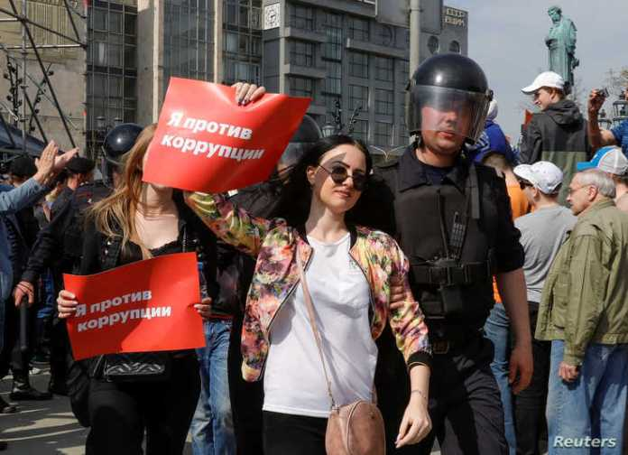 "FILE - Police officers detain opposition supporters during a protest in Moscow, Russia, May 5, 2018. The posters reads ""I am against corruption."""