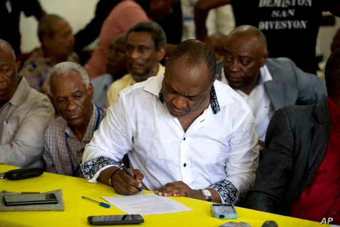 Senator Youri Latortue signs an agreement with leaders from the opposition, to choose an interim president.