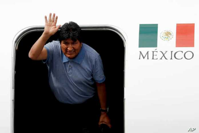 Former Bolivian President Evo Morales waves upon arrival to Mexico City, Tuesday, Nov. 12, 2019. Mexico granted asylum to
