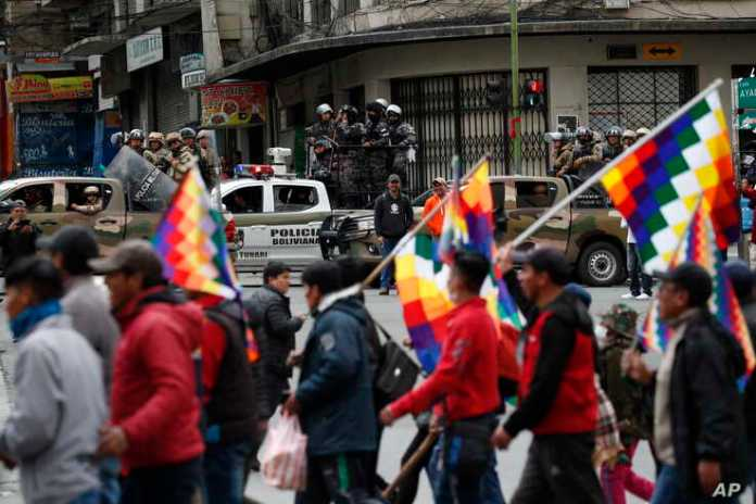 Police patrol on the sidelines of a march by supporters of former President Evo Morales, arriving from El Alto and entering La Paz, Bolivia, Nov. 12, 2019.