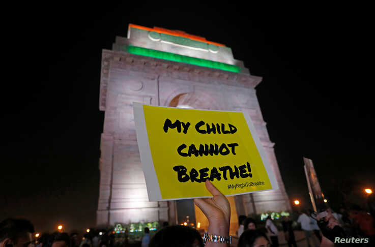 A protestor holds a placard in front of the India Gate during a protest demanding government to take immediate steps to control