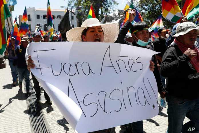 "A supporter of former President Evo Morales carries a sign reading in Spanish ""Out, Anez. Murderer"" referring to interim president Jeanine Anez during a protest in Cochabamba, Bolivia, Nov. 18, 2019."