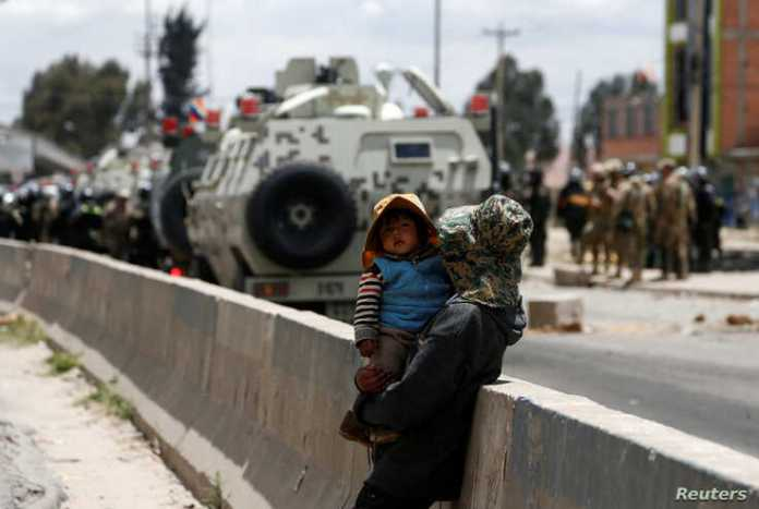 A woman carries a child as members of the security forces stand guard during a protest in Senkata, El Alto, Bolivia, Nov. 19, 2019.
