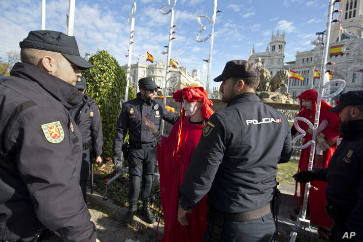 Police remove activists at the Cibeles fountain during a protest performance in Madrid, Spain, Tuesday, Dec. 3, 2019. Some 20