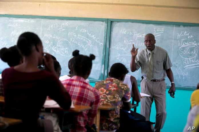 Students listen to school Director Jean Marc Charles at the Lyce school, which reopened about a week earlier than other schools in Petion-Ville, Haiti, Nov. 28, 2019.