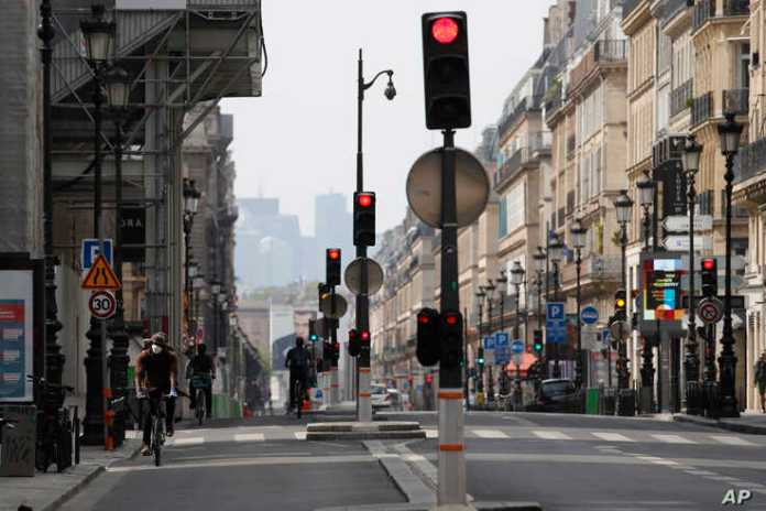 A man bikes on an empty street during a national confinement to counter COVID-19 in Paris, Tuesday April 21…