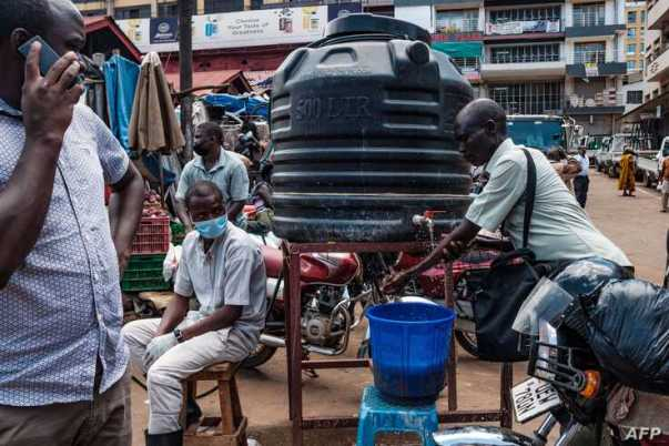 People are required to wash their hands before entering Nakasero market in Kampala on April 1 2020. - Ugandan President Yoweri…