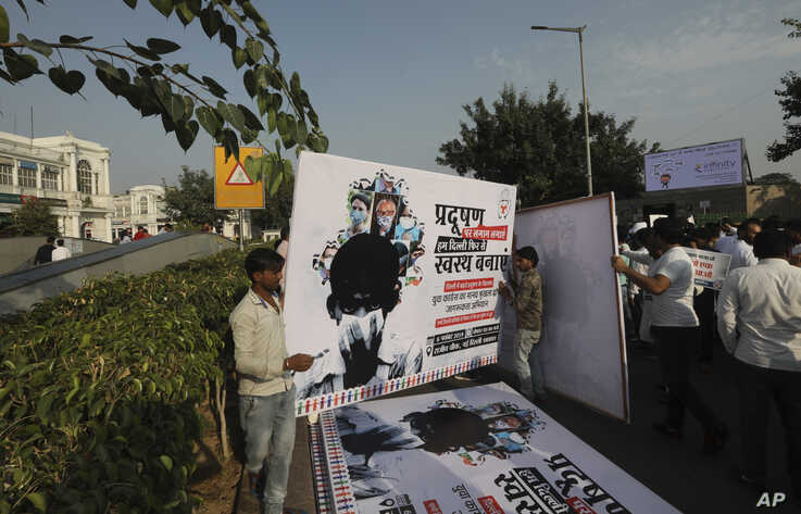 Congress party volunteers put up banners along the road for a march protesting against the alarming levels of pollution in the